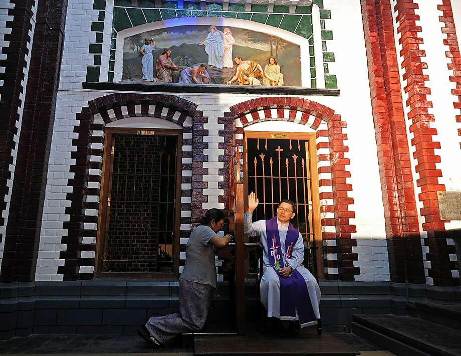 A Christian woman confesses during the Christmas eve celeberation at St Mary's cathedral in Yangon on December 24, 2012. AFP PHOTO / SOE THAN WINSoe Than WIN/AFP/Getty Images Photo: Soe Than Win, AFP/Getty Images