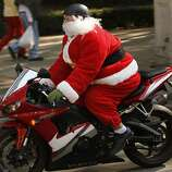 A man disguised as Santa Claus rides a motorcycle in Mexico City, Sunday, Dec. 23, 2012. (AP Photo/Marco Ugarte)
