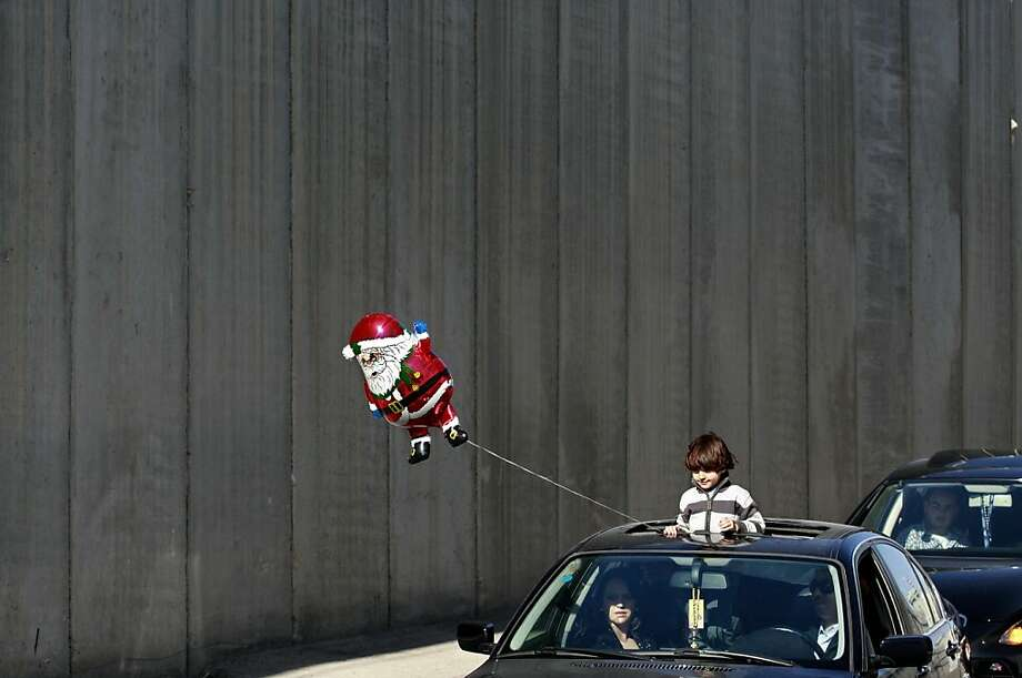 A boy holds a Santa Claus balloon from a car as the convoy of Latin Patriarch of Jerusalem Fouad Twal arrives in the West Bank town of Bethlehem for Christmas celebrations, Monday, Dec. 24, 2012. (AP Photo/Nasser Shiyoukhi) Photo: Nasser Shiyoukhi, Associated Press