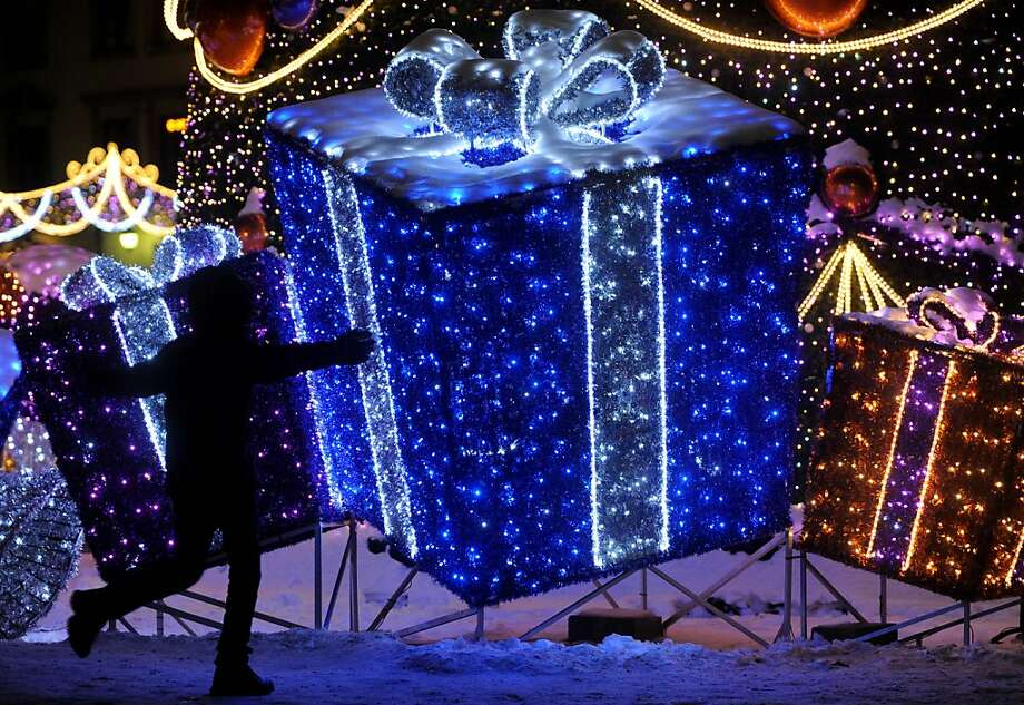 A child plays in front of a Christmas decoration resembling gifts on the Zamkowy Square in Warsaw, Poland,  Sunday, Dec 23, 2012, one day ahead of Christmas Eve. (AP Photo/Alik Keplicz) Photo: Alik Keplicz, Associated Press