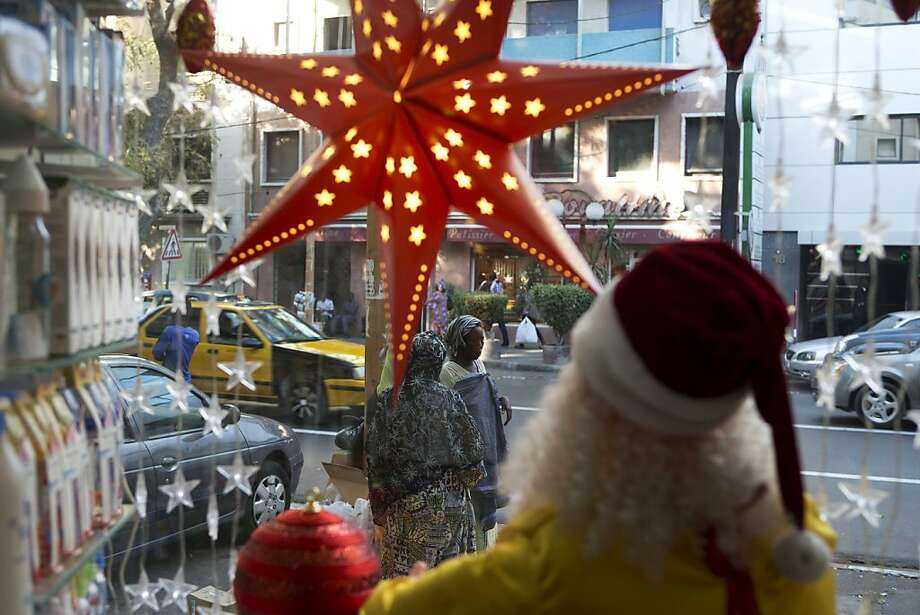 In this Tuesday, Dec. 11, 2012 photo, a pair of women beg outside a pharmacy display window decorated for Christmas, in downtown Dakar, Senegal. As Christmas approaches in mostly Muslim Senegal, vendors ply the streets selling tinsel, artificial trees, and inflatable Santas, and the main boulevards are all aglow in holiday lights. Senegal, a moderate country along Africa's western coast, has long been a place where Christians and Muslims coexist peacefully and share in each other's holidays. (AP Photo/Rebecca Blackwell) Photo: Rebecca Blackwell, Associated Press