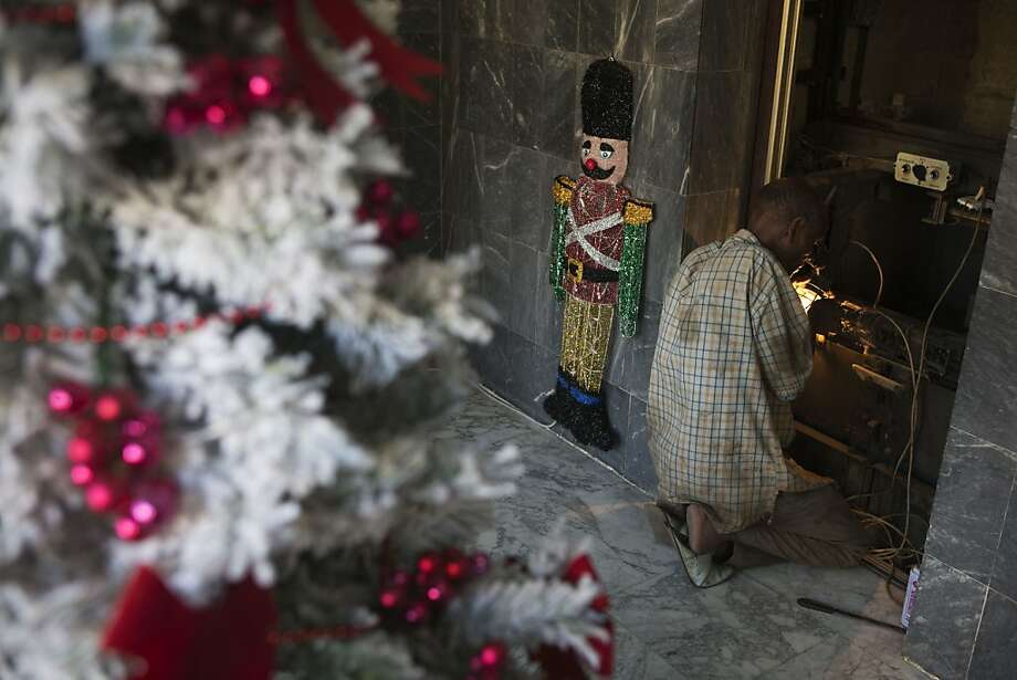 In this Tuesday, Dec. 11, 2012 photo, a repair man fixes an elevator alongside Christmas decorations, in the foyer of an apartment building in central Dakar, Senegal. As Christmas approaches in mostly Muslim Senegal, vendors ply the streets selling tinsel, artificial trees, and inflatable Santas, and the main boulevards are all aglow in holiday lights. Senegal, a moderate country along Africa's western coast, has long been a place where Christians and Muslims coexist peacefully and share in each other's holidays. (AP Photo/Rebecca Blackwell) Photo: Rebecca Blackwell, Associated Press