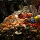 A fishmonger selects prawns for a client as part of a Christmas dinner in a market in Barcelona, Spain, Monday, Dec. 24, 2012. Retailers remain hopeful for a last-minute burst of Christmas consumerism, and some governments are encouraging it by allowing stores to open on Sunday. But with economies across the region slowing and unemployment soaring, analysts say holiday spending in Europe is bound to disappoint for the fourth year in a row. (AP Photo/Emilio Morenatti)