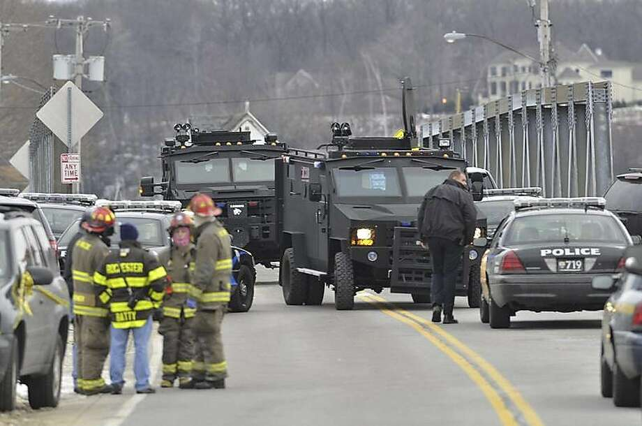 Swat teams appear at the scene of a fire in Webster, N.Y., Monday, Dec. 24, 2012. Police in New York state say a man who killed two firefighters in a Christmas Eve ambush had served 17 years for manslaughter in the death of his grandmother. (AP Photo/Messenger Post Media, Seth Binnix) Photo: Seth Binnix, Associated Press