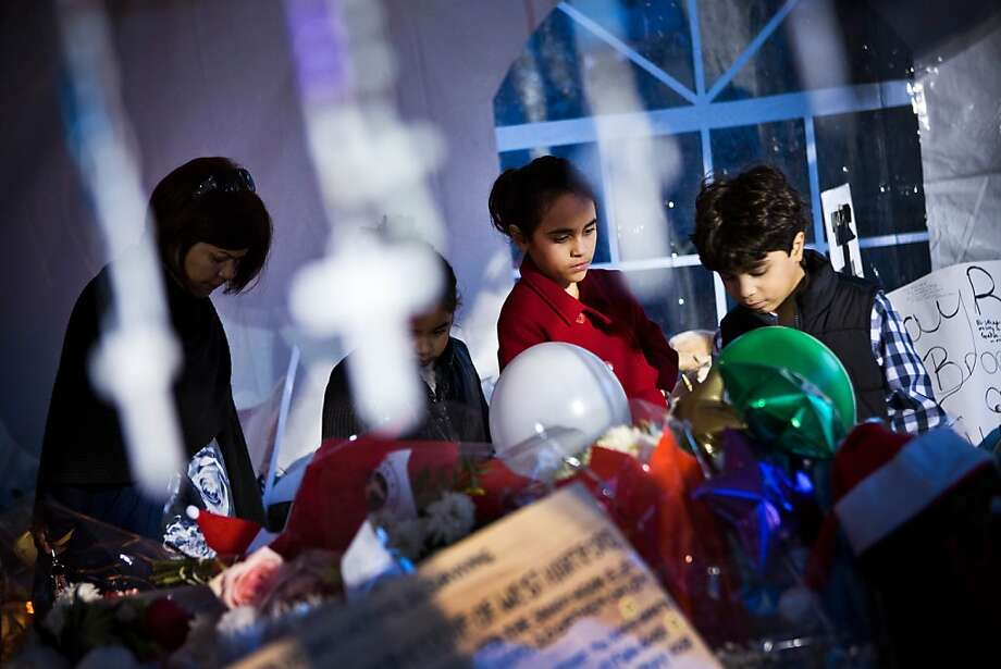 NEWTOWN, CT - DECEMBER 24:  People walk silently past a memorial for those killed in the school shooting at Sandy Hook Elementary School on December 24, 2012 in Newtown, Connecticut. Donations and letters are pouring in from across the country as the town tries to recover from the massacre. (Photo by Andrew Burton/Getty Images) Photo: Andrew Burton, Getty Images