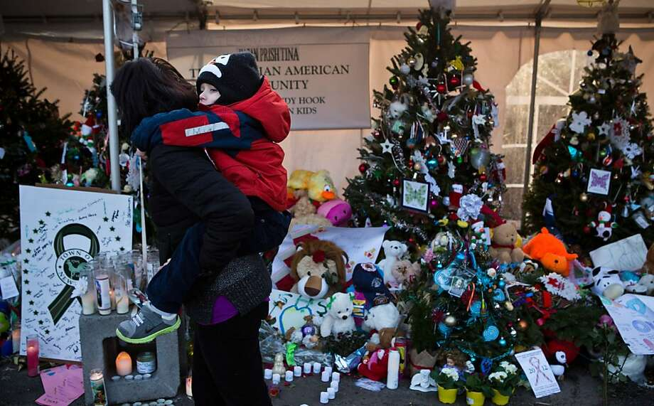 NEWTOWN, CT - DECEMBER 24:  A woman carries a child on her back while observing a memorial for those killed in the school shooting at Sandy Hook Elementary School on December 24, 2012 in Newtown, Connecticut. Donations and letters are pouring in from across the country as the town tries to recover from the massacre. (Photo by Andrew Burton/Getty Images) Photo: Andrew Burton, Getty Images