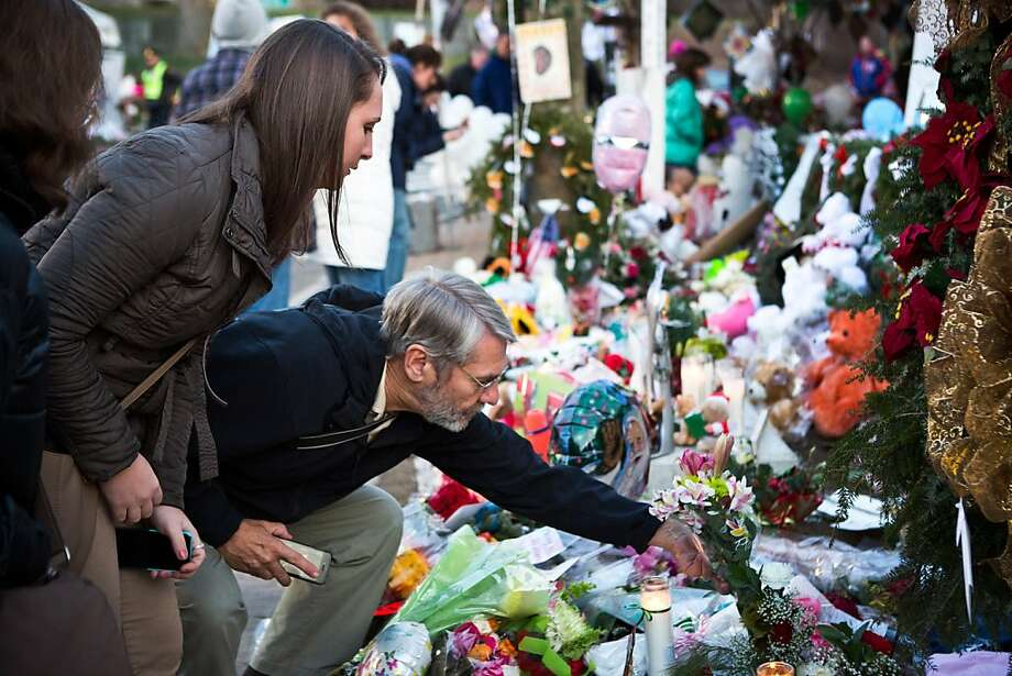 NEWTOWN, CT - DECEMBER 24:  A man lays flowers at a memorial for those killed in the school shooting at Sandy Hook Elementary School on December 24, 2012 in Newtown, Connecticut. Donations and letters are pouring in from across the country as the town tries to recover from the massacre. (Photo by Andrew Burton/Getty Images) Photo: Andrew Burton, Getty Images