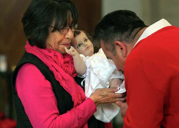 Steve Carmona, left, kisses the feet of the baby Jesus figure during the 9AM Christmas Mass at San Fernando Cathedral.  Tuesday, Dec. 25, 2012. Irma Martinez, left, holds the figure of the christ child. Photo: Bob Owen, San Antonio Express-News / © 2012 San Antonio Express-News