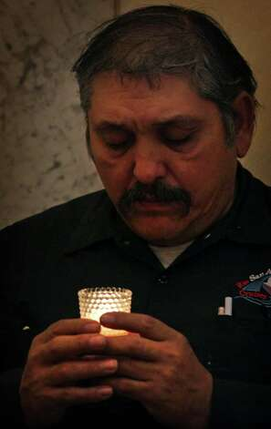 Peter Paul Ruiz prays over a  candle  during  the Mass  at San Fernando. Photo: Bob Owen, San Antonio Express-News / © 2012 San Antonio Express-News