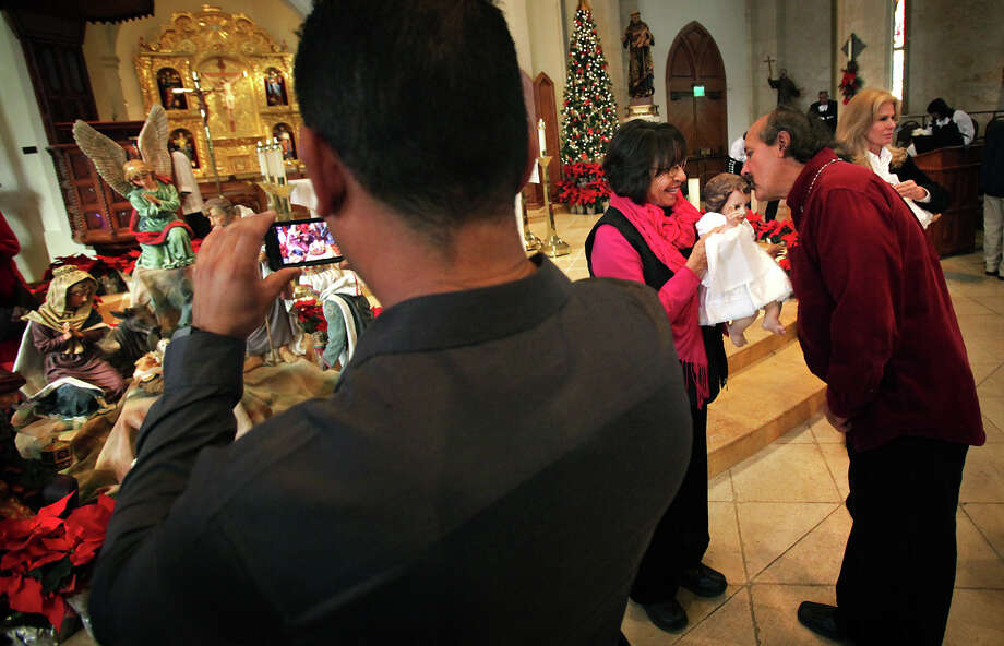 Bradford Garza kisses the head of the figure of baby Jesus while Irma Martinez holds the infant during the veneration of the Christ child at the end of the 9 a.m. Christmas Mass Service at San Fernando Cathedral. Photo: Bob Owen, San Antonio Express-News / © 2012 San Antonio Express-News