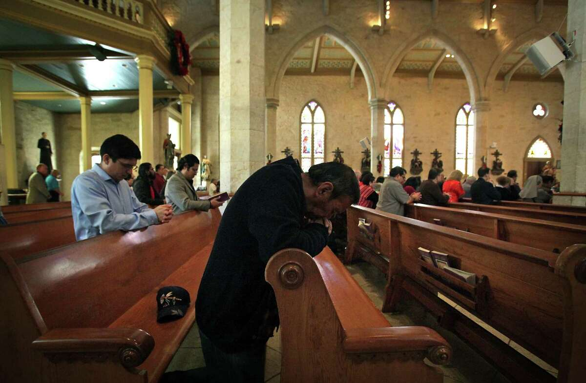 Parishioners kneel in prayer during the Christmas Mass Service at San Fernando Cathedral. Tuesday, Dec. 25, 2012.