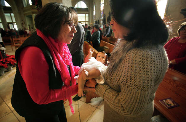 Cati Reyna, right, an Ecumenical Minister at San Fernando Cathedral, gives instructions to Irma Martinez for the veneration of the baby Jesus during the Christmas Mass Service at San Fernando Cathedral.  Tuesday, Dec. 25, 2012. Photo: Bob Owen, San Antonio Express-News / © 2012 San Antonio Express-News
