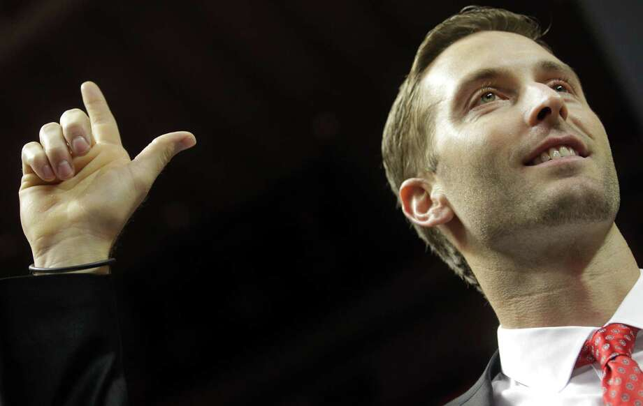 Texas Tech head coach Kliff Kingsbury gives the guns up sign during his introductory press conference in Lubbock, Texas, Friday, Dec. 14, 2012.  The Guns Up is the slogan and hand signal for Tech and is used by students and alumni as a greeting. It is also used as a victory sign during athletic events. (AP Photo/Lubbock Avalanche-Journal,Stephen Spillman) Photo: Stephen Spillman, Associated Press / Lubbock Avalanche-Journal