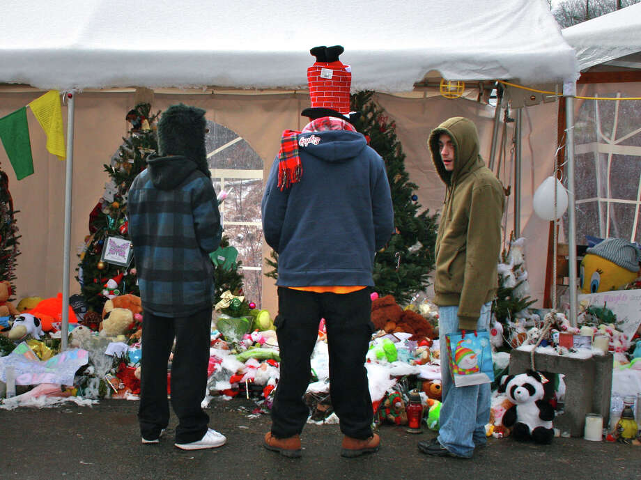 Jason Pardy, center, of Ansonia, and his two teenage sons visit a Sandy Hook memorial in Newtown on Christmas morning. Photo: Kristen V. Brown