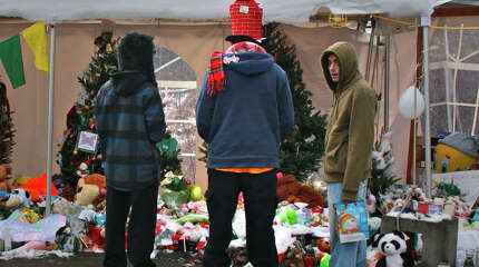 Jason Pardy, center, of Ansonia, and his two teenage sons visit a Sandy Hook memorial in Newtown on Christmas morning.