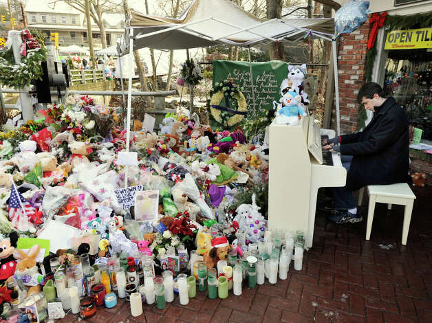 Julian Revie, of Ottawa, Canada, plays holiday music on the piano on Christmas day behind a makeshift memorial in the Sandy Hook section of Newtown for those who died in the Sandy Hook Elementary School shooting. Photo: Jason Rearick / The News-Times