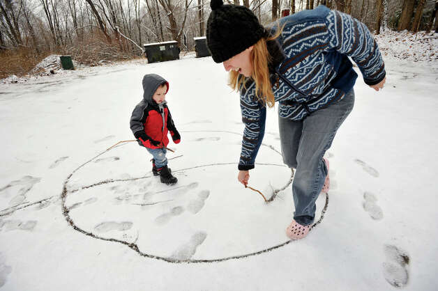 One-year-old Lucian Heydt-Moorash plays in the snow with his mother, Ava Heydt, in the parking lot of the Sandy Hook Diner in the Sandy Hook section of Newtown on Tuesday, Dec. 25, 2012. Photo: Jason Rearick / The News-Times