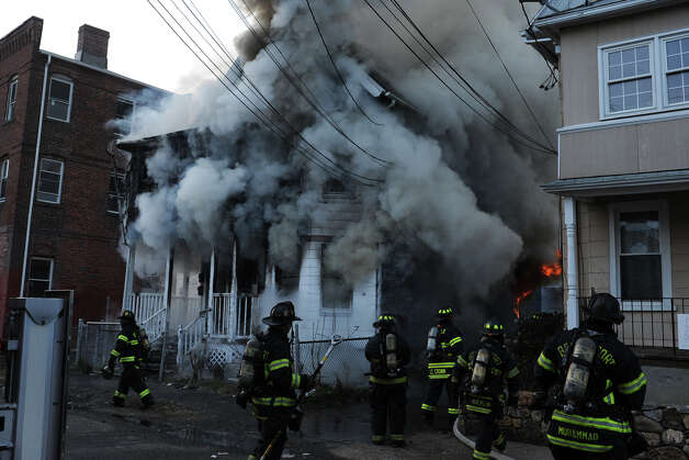 Bridgeport firefighters work on a house fire on Olive Street, in Bridgeport, Conn. on, Dec. 24th, 2012. The fire was one of three suspicious fires that broke out in a short period of time on Christams Eve afternoon. Photo: Ned Gerard