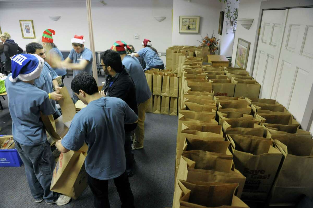 Members of Congregation Berith Sholom and their family and friends set up the paper bags that will be used to deliver food in during the Christmas Mitzvah/Holiday Meals Program at Congregation Berith Sholom on Tuesday, Dec. 25, 2012 in Troy, NY. For 19 years the congregation's members have been spending Christmas preparing meals, wrapping gifts, making holiday cards and delivering the items to shut-ins around the greater Troy area and to homeless shelters in the city. Organizers said that this year they will deliver the meals and gifts to 380 people, an increase of over 100 people in the last two years. The over 160 households that make up the congregation take part all year long buying gifts and collecting items and donating money towards the meals program. (Paul Buckowski / Times Union)