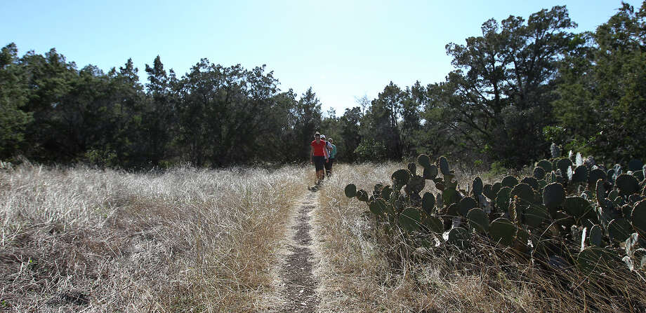 A trio of hikers walk along a trail at Government Canyon State Natural Area. The park will stay open every day from Christmas through Jan. 7 in an effort to attract more visitors to the 8,000-acre park. Photo: Kin Man Hui, San Antonio Express-News / ©2012 San Antonio Express-News