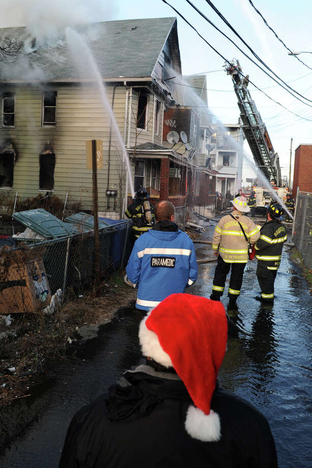 Antonio Vargas, of Bridgeport, watches as Bridgeport firefighters work on a fire in a home on Madison Court, in Bridgeport, Conn. on, Dec. 24th, 2012. The fire was one of three suspicious fires that broke out in a short period of time on Christams Eve afternoon. Photo: Ned Gerard