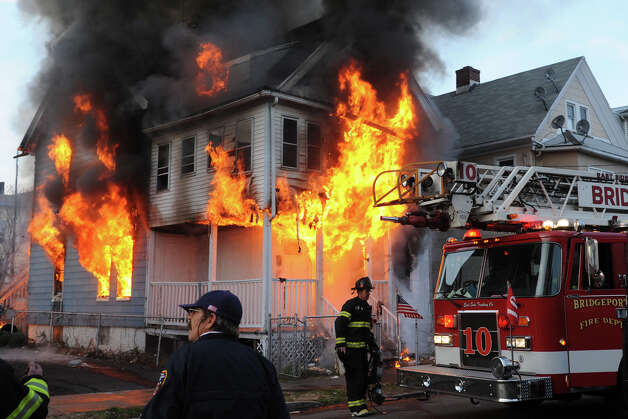 Bridgeport firefighters arrive at house fire on Olive Street, in Bridgeport, Conn. on, Dec. 24th, 2012. The fire was one of three suspicious fires that broke out in a short period of time on Christams Eve afternoon. Photo: Ned Gerard