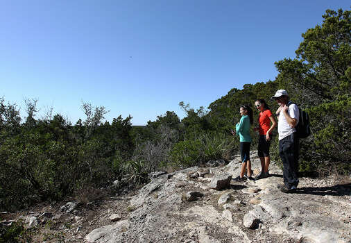 Don (from left), Alex and her friend Rachel (last names withheld) reach the top of a bluff during a hike on a trail at Government Canyon State Park on Tuesday, Dec. 25, 2012. The park remained open from Christmas until January 7th in an effort to attract more visitors as well as to validate funding for the parks by the legislature. The trio of hikers were amongst a small group of people who took advantage of the mild temperatures on Christmas day to visit the park. Photo: Kin Man Hui, San Antonio Express-News / ©2012 San Antonio Express-News