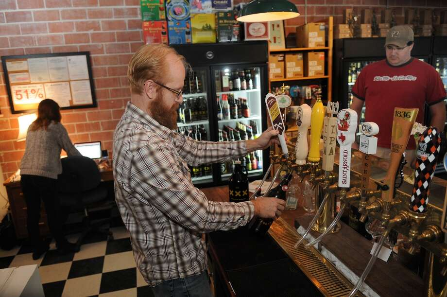 Premium Draught owner Johnny Orr fills a growler for Jason Grant at a new Heights business. Photo: Jerry Baker, Freelance