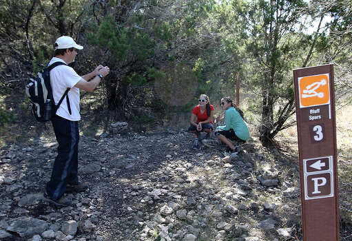 Don (from left) take a picture of Alex and Rachel (last names withheld) during a hike on a trail at Government Canyon State Park on Tuesday, Dec. 25, 2012. The park remained open from Christmas until January 7th in an effort to attract more visitors as well as to validate funding for the parks by the legislature. The trio of hikers were amongst a small group of people who took advantage of the mild temperatures on Christmas day to visit the park. Photo: Kin Man Hui, San Antonio Express-News / ©2012 San Antonio Express-News