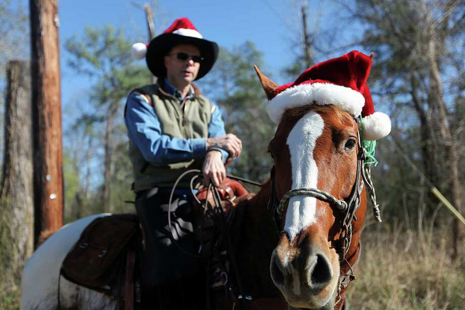 Dion Bandenbosch and his horse 'Fire in the Wind' both wear Santa hats as they take a Christmas Day ride along FM 1486 on Tuesday, Dec. 25, 2012, near Montgomery, Texas. Photo: Mayra Beltran, Houston Chronicle / © 2012 Houston Chronicle