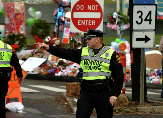 Monroe police officer John McAulay directs traffic at the site of the massive memorial setup in downtown Newtown on Christmas Day in Newtown, Conn. on Tuesday December 25, 2012. Police from other towns around the region came in to relieve Newtown officers for the holiday. Photo: Christian Abraham / Connecticut Post