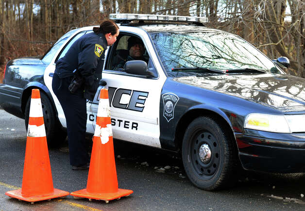 A Monroe police officer confers with a Manchester police officer in their vehicle near the Sandy Hook Volunteer Fire and Rescue builing as police from other towns around the region came in to relieve Newtown officers on Christmas Day in Newtown, Conn. on Tuesday December 25, 2012. Photo: Christian Abraham / Connecticut Post