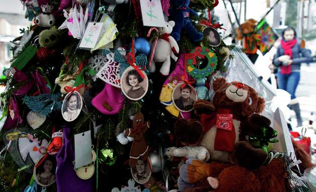 Portraits of slain students and teachers hang from a tree at a memorial in Newtown, Conn. Tuesday, Dec. 25, 2012. People continue to visit memorials in the wake of the shootings after gunman Adam Lanza walked into Sandy Hook Elementary School in Newtown, Conn., Dec. 14, and opened fire, killing 26, including 20 children, before killing himself.  (AP Photo/Craig Ruttle) Photo: Craig Ruttle, Associated Press / FR61802 AP