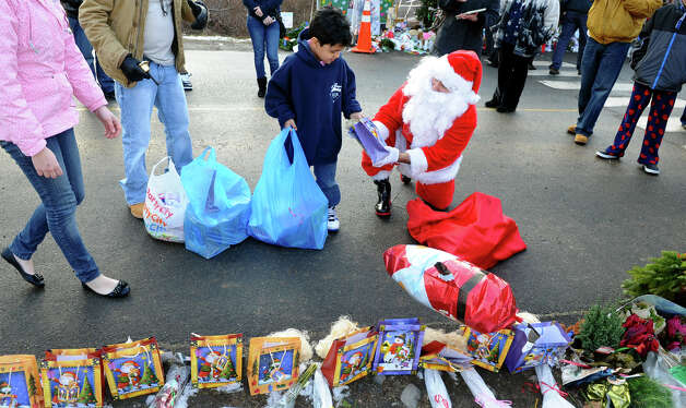 A Santa portrayed by Bridgeport resident Eustaquio Pena gives a gift bag to his helper Olicio Fernandez, of Bridgeport, to add to the memorial, after coming to the memorial set up at the Sandy Hook Volunteer Fire and Rescue building to give gift bags to children and leave items in memory of the Sandy Hook shooting victims on Christmas Day in Newtown, Conn. on Tuesday December 25, 2012. Photo: Christian Abraham / Connecticut Post