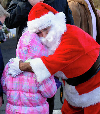 A Santa portrayed by Bridgeport resident Eustaquio Pena hugs Ajla Brescic, 6, of Stanhope, NJ, after he came to the memorial set up at the Sandy Hook Volunteer Fire and Rescue building to give gift bags to children and leave items in memory of the Sandy Hook shooting victims on Christmas Day in Newtown, Conn. on Tuesday December 25, 2012. Photo: Christian Abraham / Connecticut Post