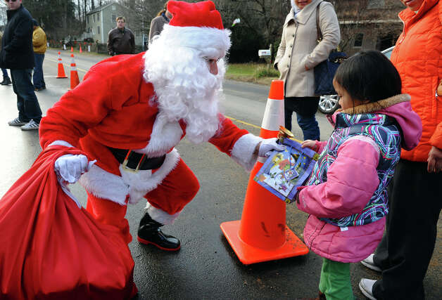 A Santa portrayed by Bridgeport resident Eustaquio Pena gives a gift bag to Adlin Rizal, 4, of West haven, after he came to the memorial set up at the Sandy Hook Volunteer Fire and Rescue building to give gift bags to children and leave items in memory of the Sandy Hook shooting victims on Christmas Day in Newtown, Conn. on Tuesday December 25, 2012. Photo: Christian Abraham / Connecticut Post