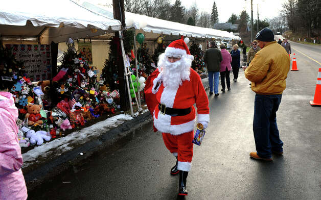 A Santa portrayed by Bridgeport resident Eustaquio Pena arrives at the memorial set up at the Sandy Hook Volunteer Fire and Rescue building to give gift bags to children and leave items in memory of the Sandy Hook shooting victims on Christmas Day in Newtown, Conn. on Tuesday December 25, 2012. Photo: Christian Abraham / Connecticut Post