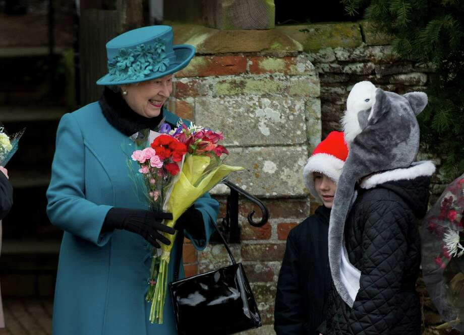 Britain's Queen Elizabeth II receives flowers from children after attending the British royal family's traditional Christmas Day church service in Sandringham, England, Tuesday, Dec. 25, 2012.  (AP Photo/Matt Dunham) Photo: Matt Dunham