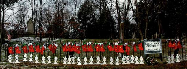 Stockings  and angel silhouettes honoring Sandy Hook Elementary School students and teachers line an iron fence in Newtown, Conn. Photo: Craig Ruttle, Associated Press / FR61802 AP