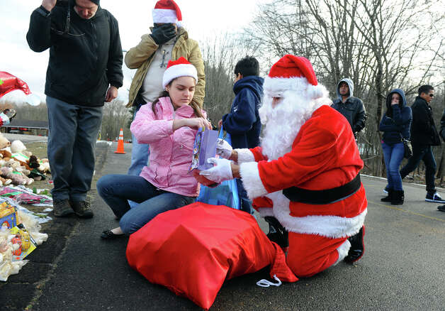 A Santa portrayed by Bridgeport resident Eustaquio Pena and his wife Fernanda Olivera, left, came to the memorial set up at the Sandy Hook Volunteer Fire and Rescue building to give gift bags to children and leave items in memory of the Sandy Hook shooting victims on Christmas Day in Newtown, Conn. on Tuesday December 25, 2012. Photo: Christian Abraham / Connecticut Post