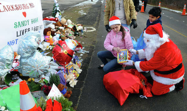 A Santa portrayed by Bridgeport resident Eustaquio Pena and his wife Fernanda Olivera, came to the memorial set up at the Sandy Hook Volunteer Fire and Rescue building to give gift bags to children and leave items in memory of the Sandy Hook shooting victims on Christmas Day in Newtown, Conn. on Tuesday December 25, 2012. Photo: Christian Abraham / Connecticut Post