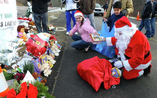 A Santa portrayed by Bridgeport resident Eustaquio Pena and his wife Fernanda Olivera, center, came to the memorial set up at the Sandy Hook Volunteer Fire and Rescue building to give gift bags to children and leave items in memory of the Sandy Hook shooting victims on Christmas Day in Newtown, Conn. on Tuesday December 25, 2012. Photo: Christian Abraham / Connecticut Post