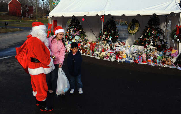 A Santa portrayed by Bridgeport resident Eustaquio Pena came to the memorial set up at the Sandy Hook Volunteer Fire and Rescue building to give gift bags to children and leave items in memory of the Sandy Hook shooting victims on Christmas Day in Newtown, Conn. on Tuesday December 25, 2012. Photo: Christian Abraham / Connecticut Post