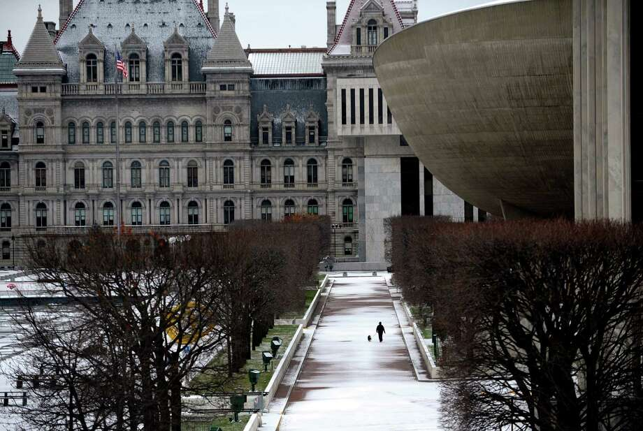 A light covering of snow makes for a white Christmas morning at the Empire State Plaza with the capitol building seen in the background on Tuesday. More snow is expected to fall Wednesday evening. (Paul Buckowski / Times Union) Photo: Paul Buckowski  / 00020571A
