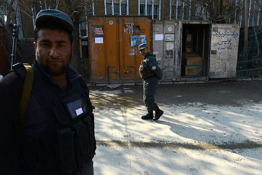 Officers stand guard in Kabul where a female police officer killed an American civilian adviser. Photo: Shah Marai, AFP/Getty Images