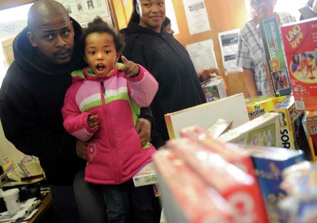 "Four-year-old Gabrielle Bascome, with her father Rashean, points to a Christmas gift that caught her eye Tuesday, Dec. 25, 2012 during ""Santa's Last Stop,""  an annual event organized by the East End Community Council to provide toys to anyone in need on Christmas morning. Photo: Autumn Driscoll / Connecticut Post"
