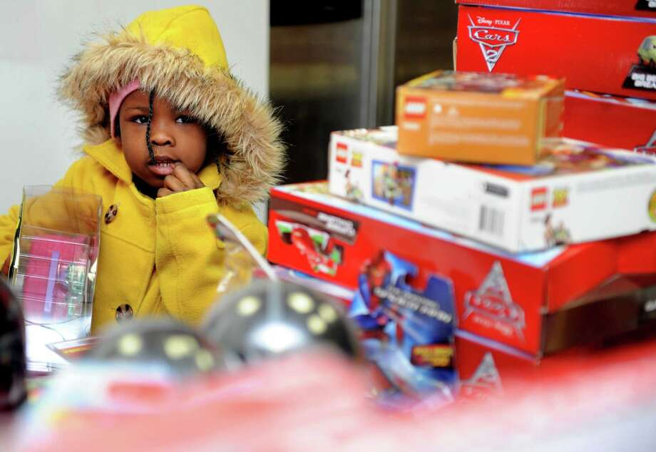 "Four-year-old Aaliyah Johnson picks out a Christmas gift Tuesday, Dec. 25, 2012 during ""Santa's Last Stop,""  an annual event organized by the East End Community Council to provide toys to anyone in need on Christmas morning. Photo: Autumn Driscoll / Connecticut Post"