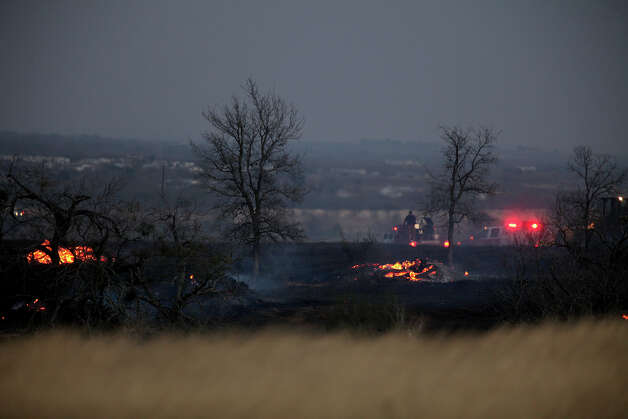 Firefighters work at the scene of a brush fire that burned about 350 acres in eastern Bexar County. Photo: Lisa Krantz, San Antonio Express-News / © 2012 San Antonio Express-News