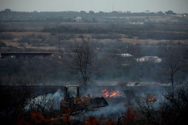Firefighters work at the scene of a brush fire that burned about 350 acres in east Bexar County near Converse, Tuesday, Dec. 25, 2012. Photo: Lisa Krantz, San Antonio Express-News / © 2012 San Antonio Express-News