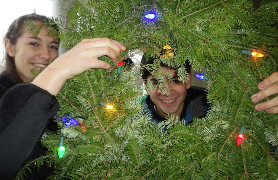 Casey Boatwright, 17, holds a Christmas wreath that frames fellow Fairfield Ludlowe High School Key Club member Joel Villalba, 17. On Sunday, they were among about a dozen others who decorated wreaths and placed them on houses severely damaged by Superstorm Sandy.  Fairfield CT 12/16/12 Photo: Meg Barone / Fairfield Citizen freelance